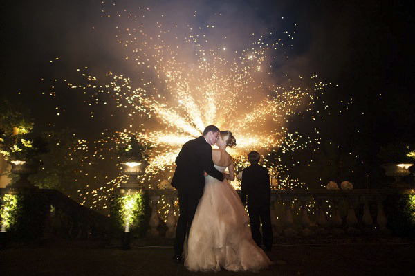 couple kissing in front of fireworks, photo by Magnus Bogucki | via junebugweddings.com