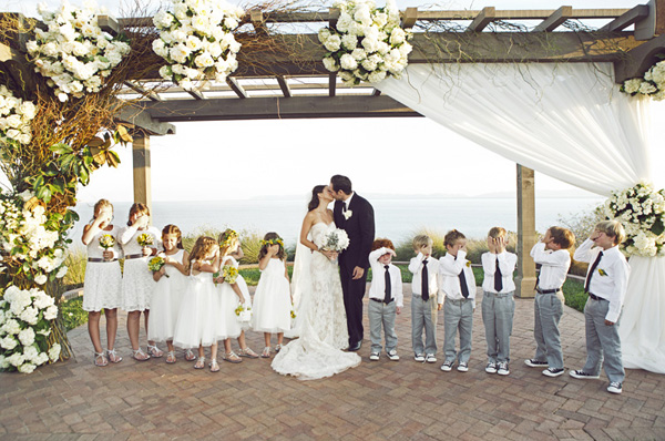 couple kissing with boys and girls covering their eyes, wedding party photo by Duke Images | via junebugweddings.com