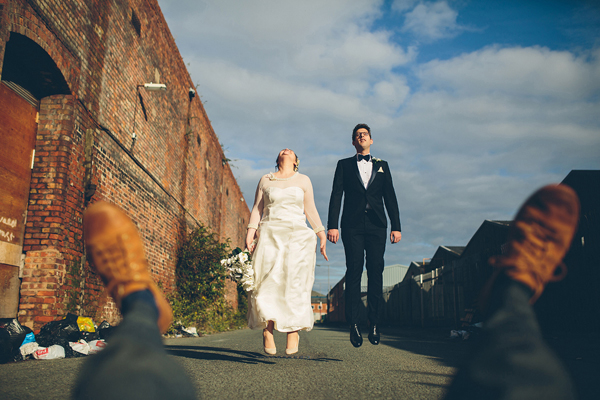 hilarious jumping bride and groom, photo by Liam Crawley of CG Weddings by The Crawleys - England | via junebugweddings.com