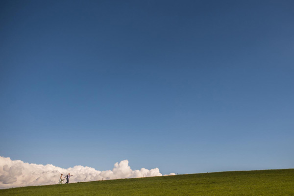 blue clouds and green grass horizon line, wedding photo by Savo Photography | via junebugweddings.com