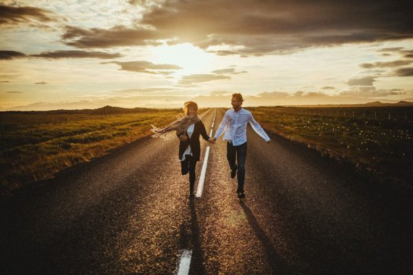 couple running down a road at sunset SEO tips for wedding photographers