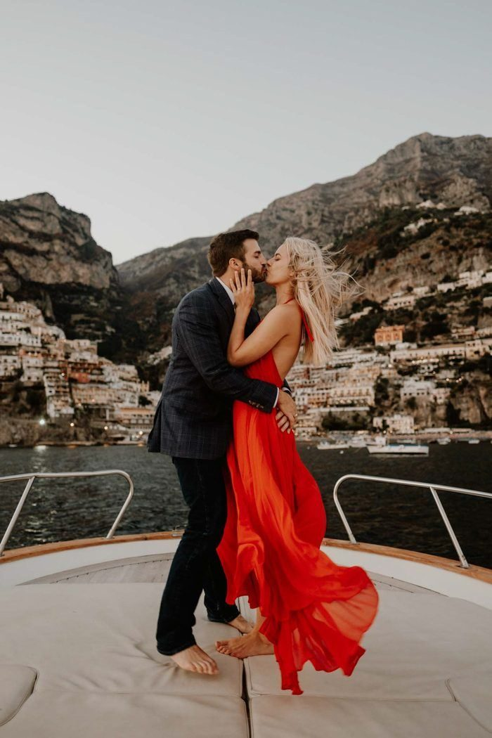 engaged couple kissing on a boat