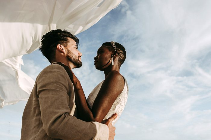 Couple embracing while a sheet blows in the wind behind them
