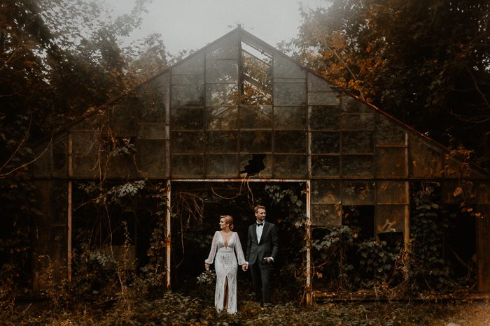 couple looking off in the distance holding hands in front of greenhouse –using pinterest
