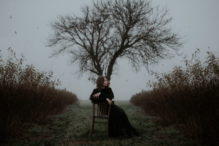 dark and moody woman in front of tree