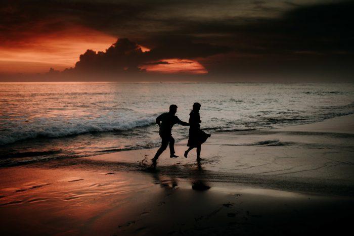 couple running on beach golden hour