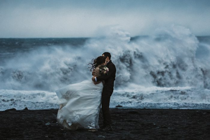 Top pic of the Month rough wave breaking behind couple