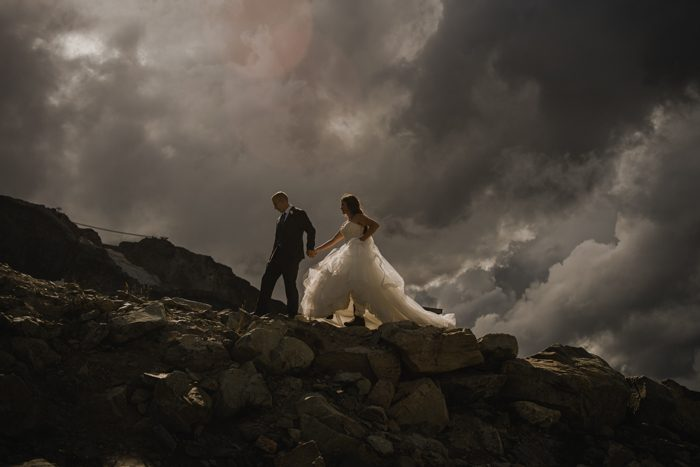 wedding couple walking up mountain