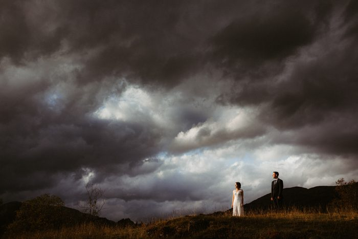 stormy weather above bride and groom