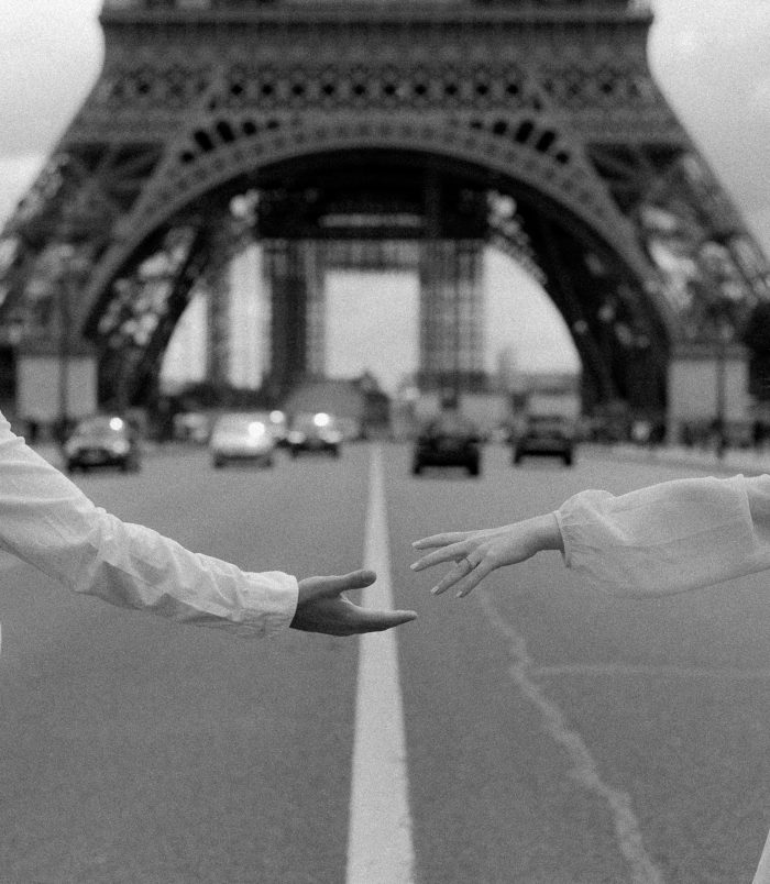 couple reaching hands in front of Eiffel Tower