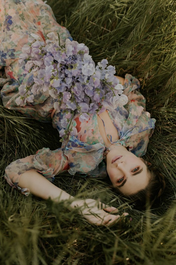 girl in floral dress laying in grass