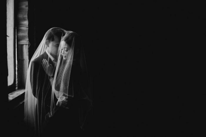 black and white photo couple under veil