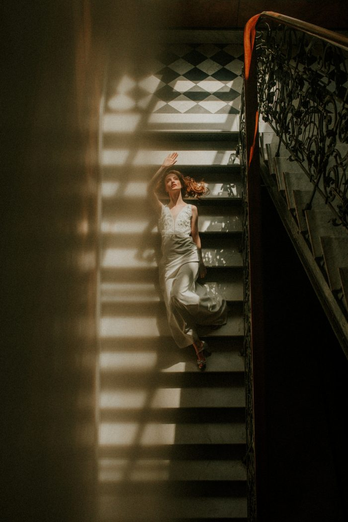 moody photo of bride laying on staircase