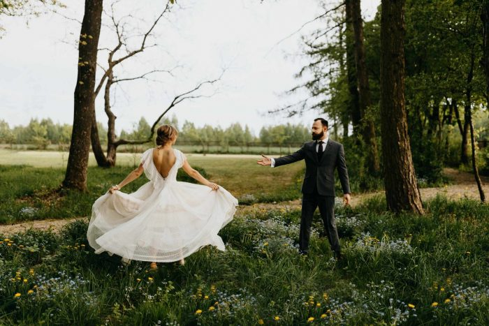 wedding couple in field with flowers and trees