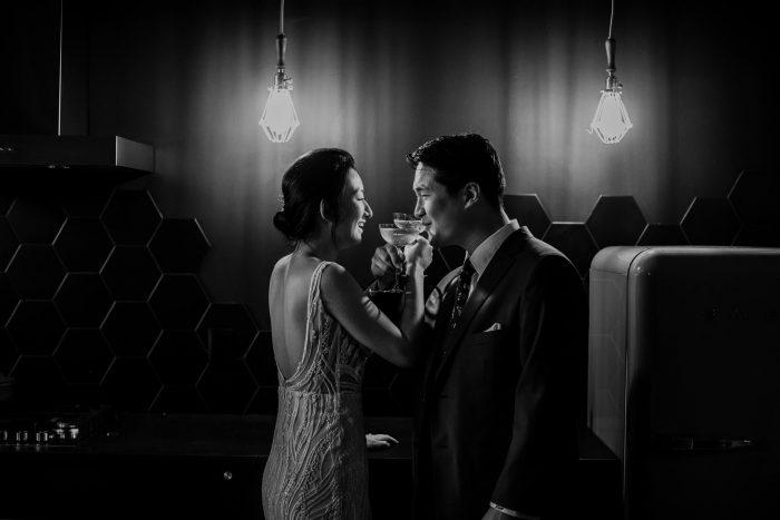 black and white photo wedding couple making toast