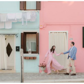 couple walking in front of colorful buildings