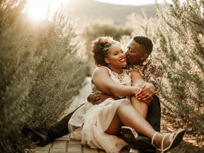 couple sitting embracing to write wedding photographer bio