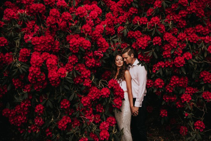 couple among bright red flowers
