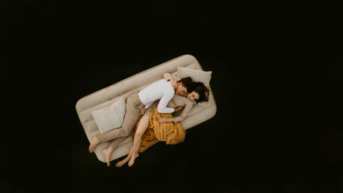 couple floating on inflatable mattress in river