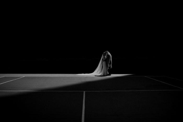 black and white wedding portrait on tennis court