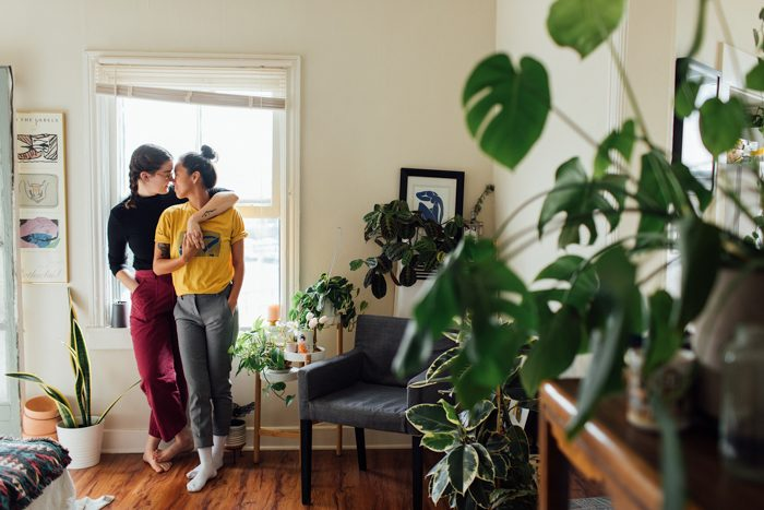 couple embracing near window with plants nearby discussing business finance tips