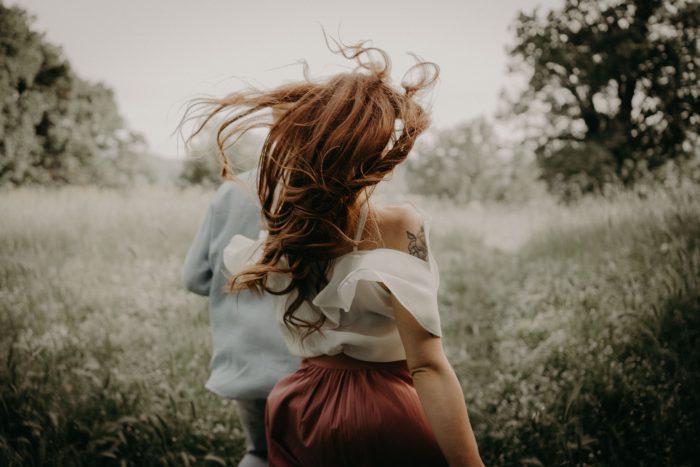couple running through meadow