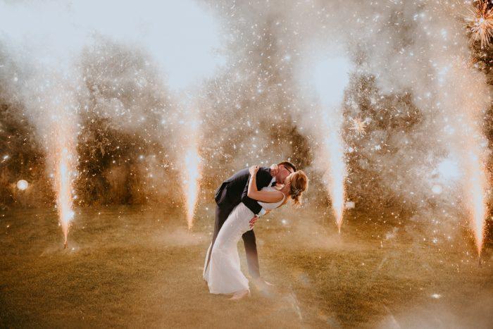fireworks behind wedding day couple