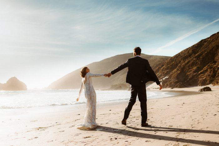 wedding day couple running on beach