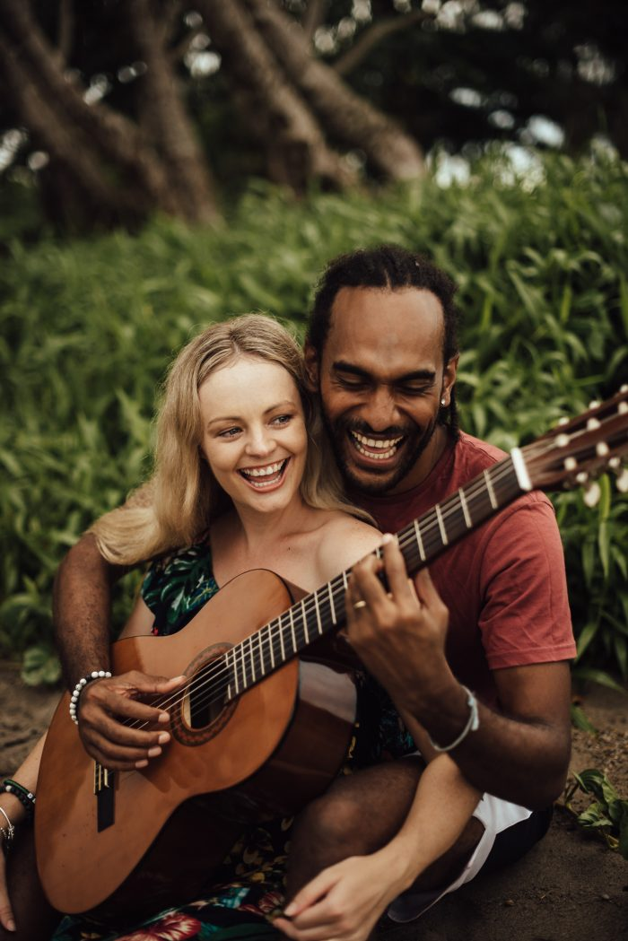 happy couple playing guitar