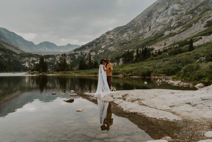 wedding day portrait by lake and mountains