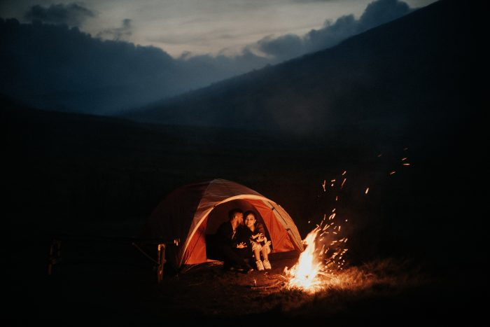 couple inside tent by campfire