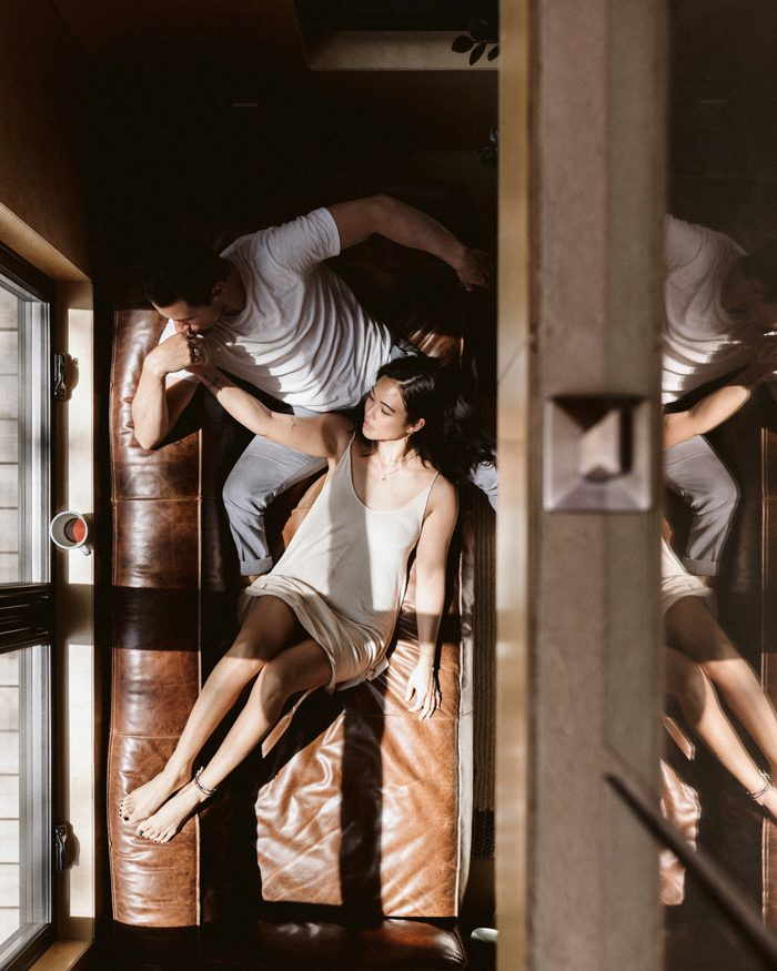 couple laying on couch by window